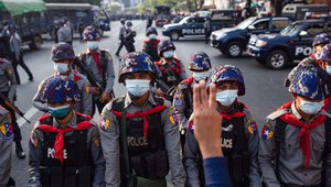 Riot police stand on guard in front of the Central Bank building during a demonstration in Myanmar, February 2021