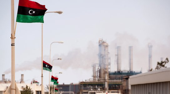 Libyan flag flutters outside an oil refinery in Zawiya on September 23, 2011