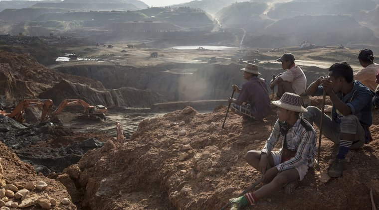 Freelance Yemase miners sit on the top of a hill in Hpakant, Myanmar