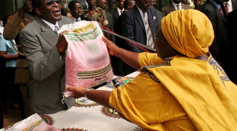 Robert Mugabe, hands out maize seed to a Zanu PF supporter