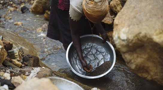 Woman panning for cassiterite DRC