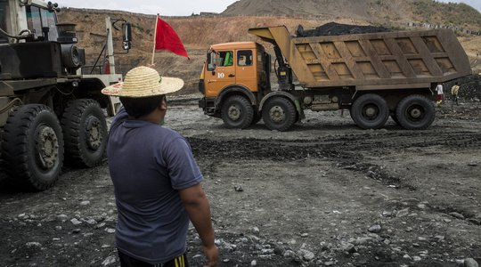 Minzayar Myanmar mining - man with red flag in front of dump truck