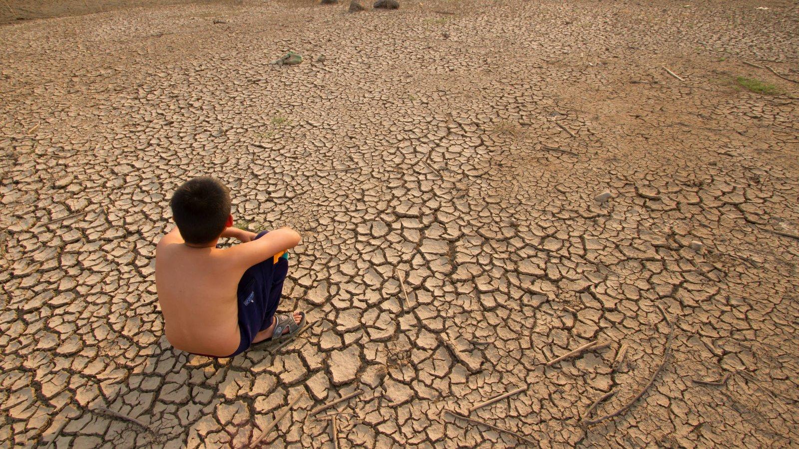 Child sits on cracked earth. Copyright: piyaset/iStockPhoto